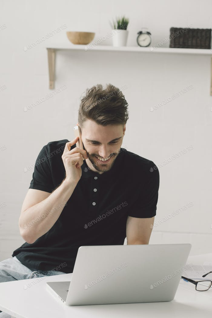 Hombre guapo con portátil en casa. Retrato masculino freelance casa de trabajo