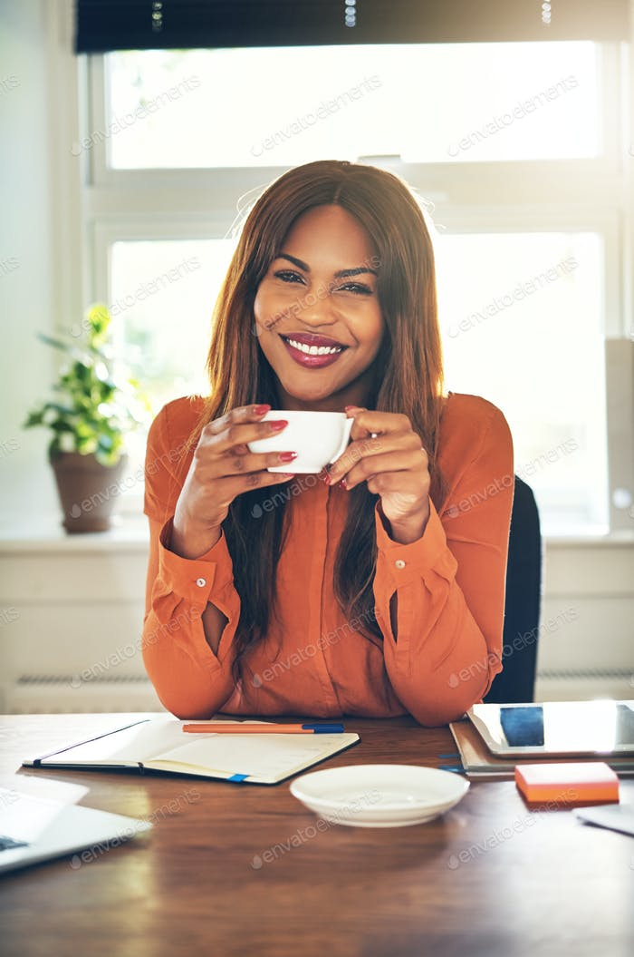 Smiling young female entrepreneur drinking coffee while working from home