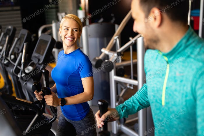 Happy people working out on treadmills in the gym