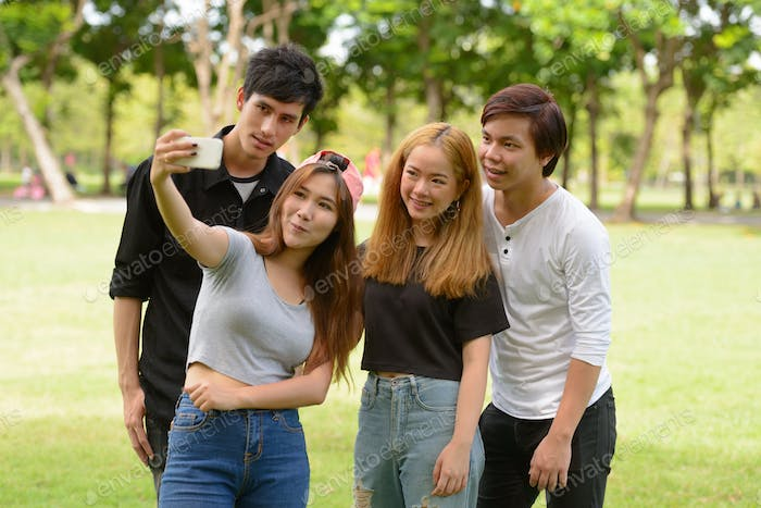 Happy young group of friends taking selfie together at the park
