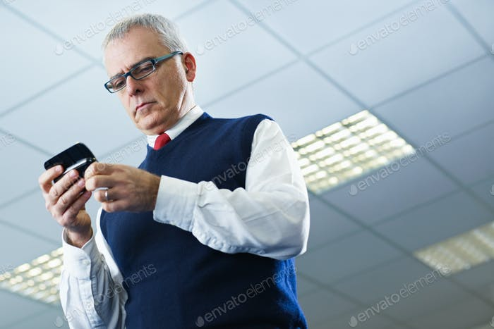 mature businessman reading e-mails on cellphone