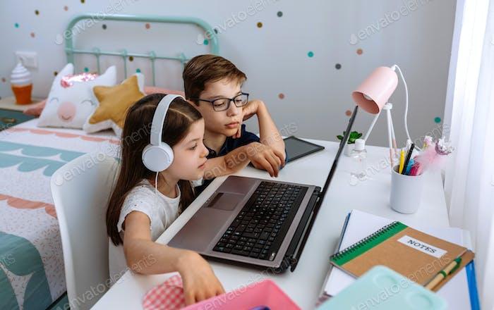 Junge hilft seiner Schwester beim Lernen mit Computer