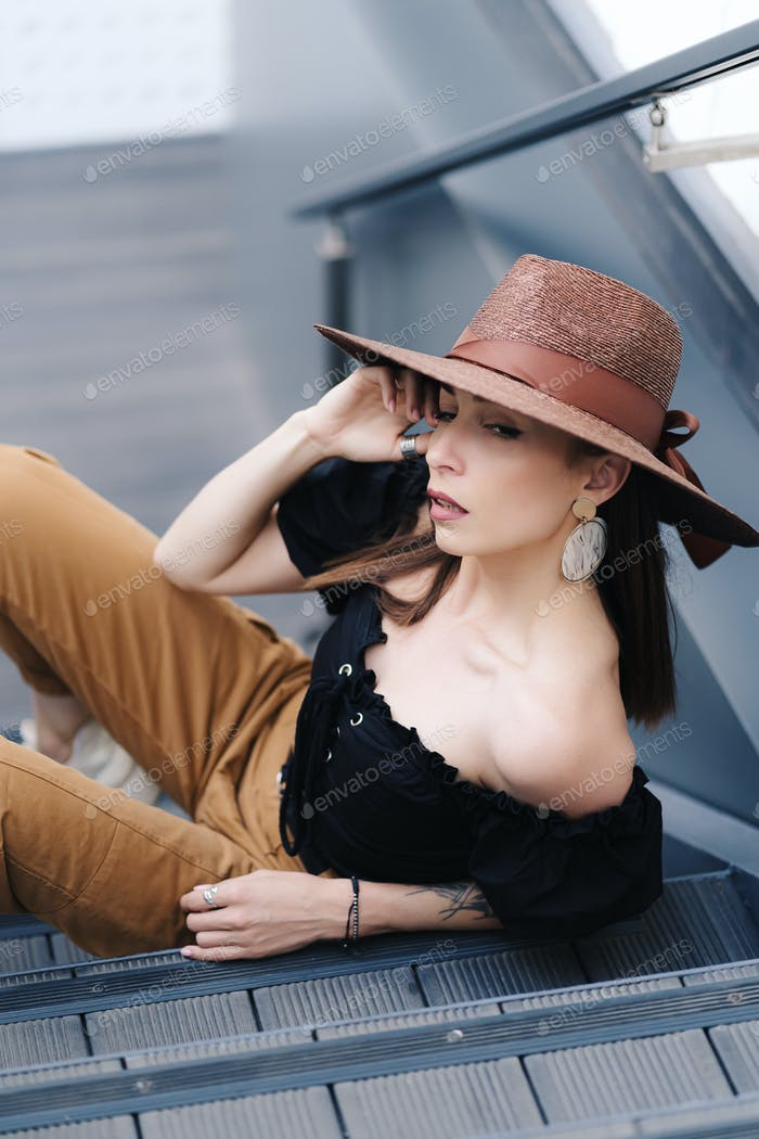 Fashionable brunette woman with long hair, wearing stylish large wicker hat, posing on the stairs