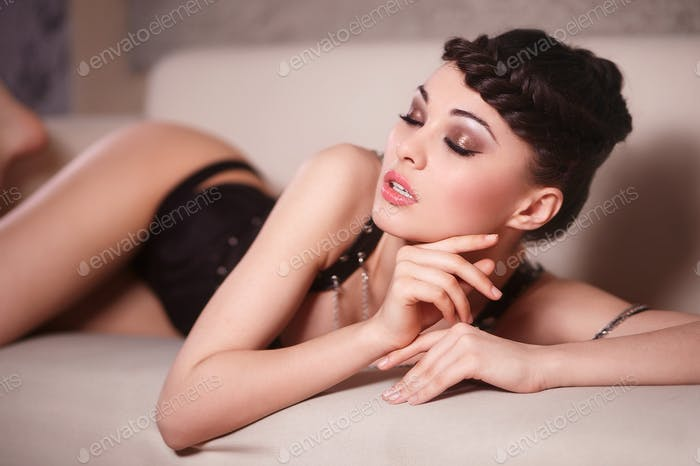 Beautiful sexy fashion girl in black corset lying on the sofa indoors bright makeup and hairstyle