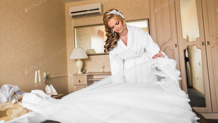 bride with wedding makeup and hairstyle in bedroom