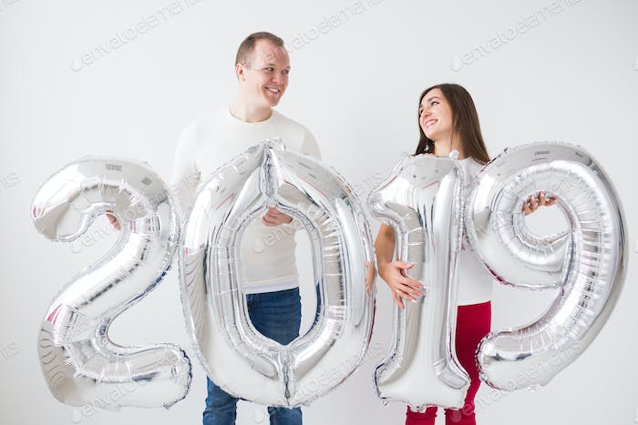 New year, celebration and holidays concept - Surprised love couple holding sign 2019 made of silver
