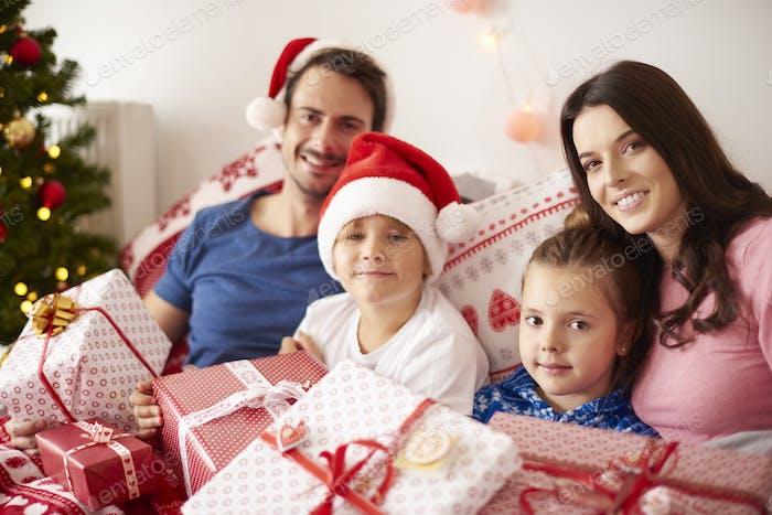 Family spending Christmas morning in bed