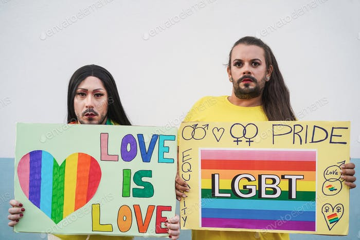 Drag queens holding lgbt banners outdoors at pride protest - Focus on faces