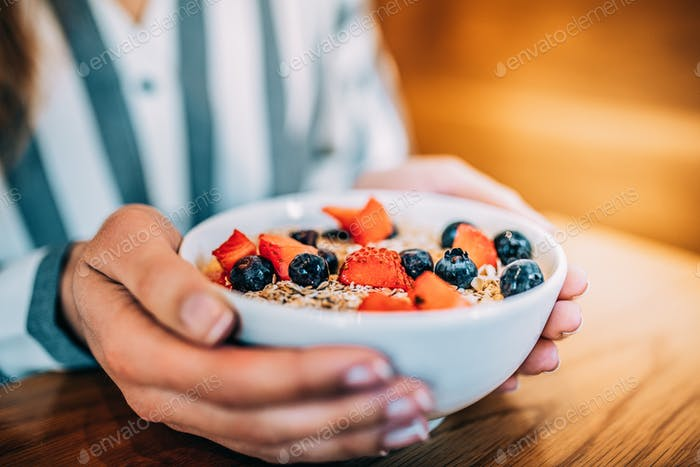 Crop woman close up eating oat and fruits bowl for breakfast