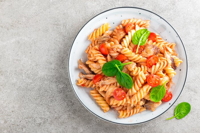 Pasta spirali stirred with fried pieces of chicken, cherry tomatoes and tomato sauce