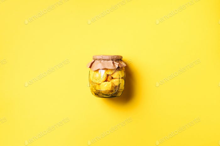 Pickled squash in glass jar over yellow background. Top view. Flat lay. Copy space. Canned and