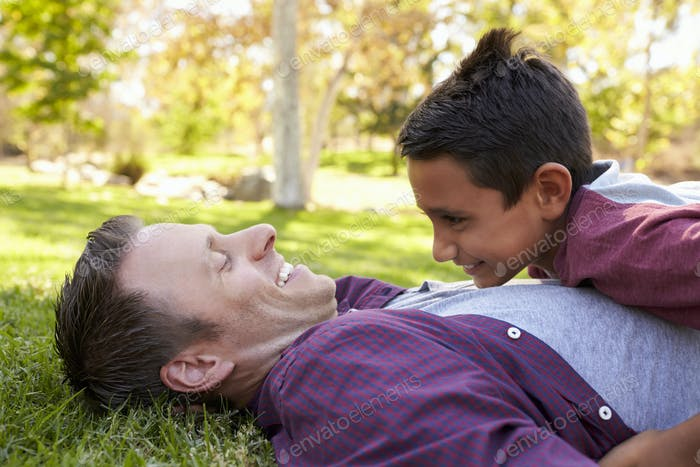 Mixed race Asian boy lying on top of his dad in a park