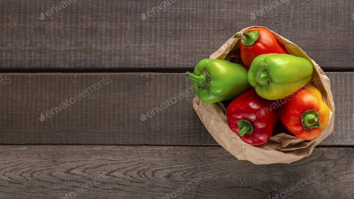 Big paper bag with paprika on wooden background