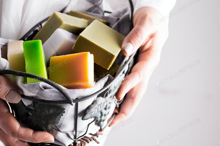 A woman holding handcrafted olive oil soap in basket . Handmade zero waste concept