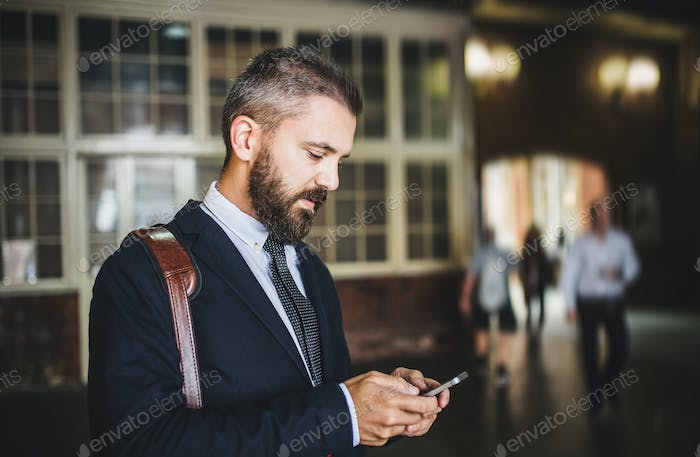 A hipster businessman with smartphone standing indoors in the city, texting.