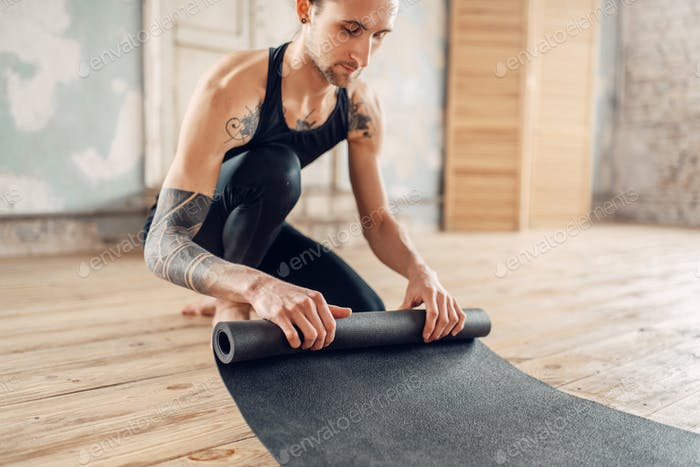 Male yoga with tattoo prepares mat for training