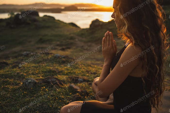 Woman praying alone at sunrise. Nature background. Spiritual and emotional concept.