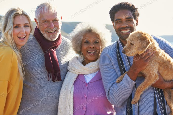 Portrait Of Senior Couple Walking Along Shoreline With Adult Offspring
