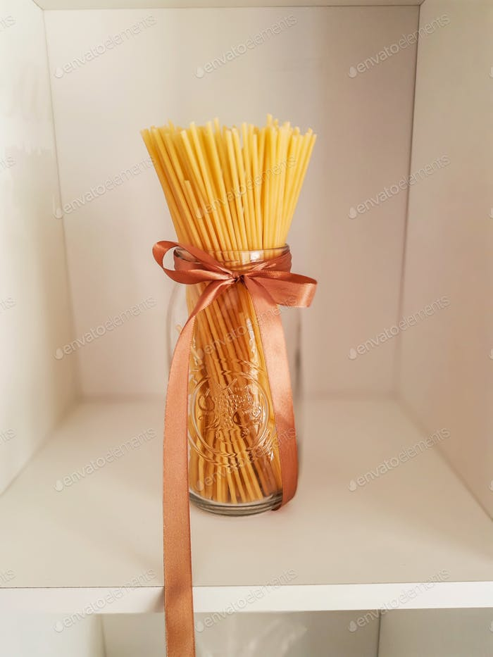 Artisanal spaghetti pasta in glass with bow in a local shop