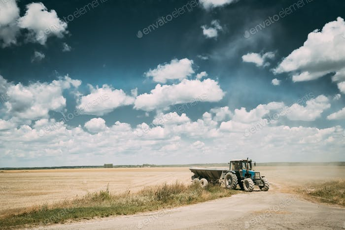 Tractor With Cart In Motion On Country Road In Summer Season. Ag