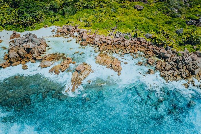 Aerial top view of beautiful tropical Anse Marron beach. Ocean waves hitting granite rocks along