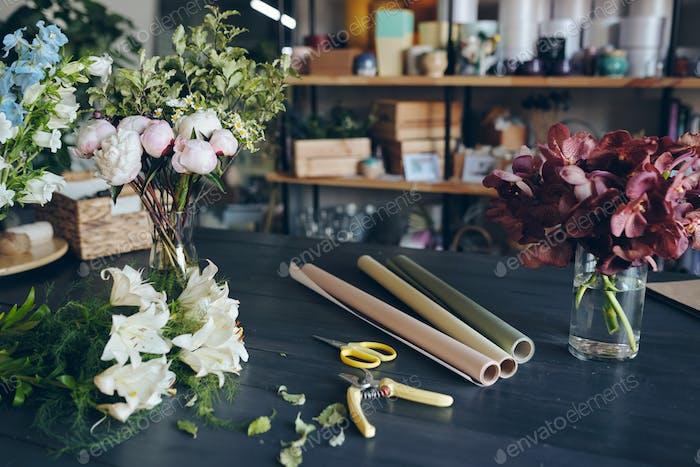 Close-up of flowers in vases, secateurs, scissors