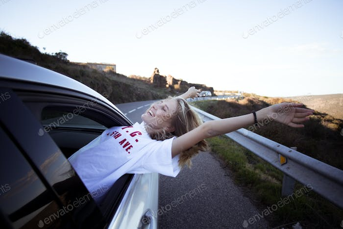 Woman in car road trip waving out window smiling