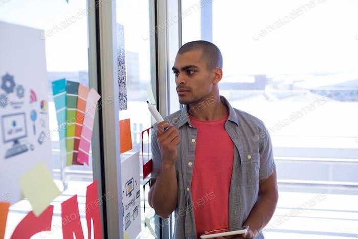 Männlich Executive lesen Haftnotizen auf Glastür