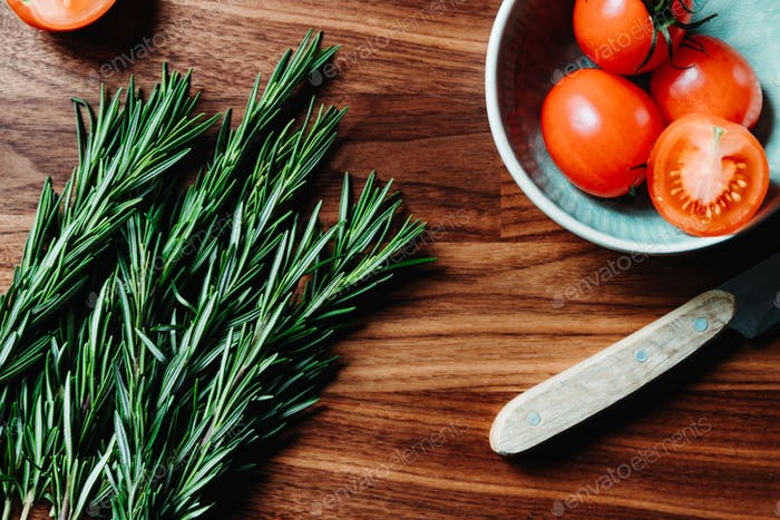 Lifestyle photo of cooking healthy eating with tomatoes and fresh rosemary