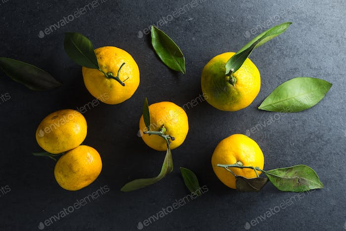 Fresh yellow tangerines on a gray stone
