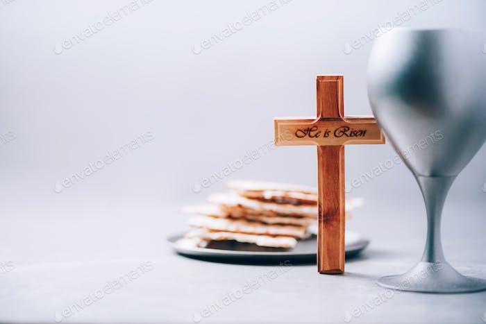 Matzos ungesäuertes Brot, Kelch aus Wein, Holzkreuz auf grauem Hintergrund. Christliche Gemeinschaft für