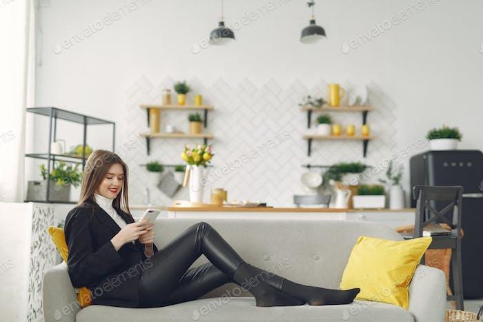 Chica sentada en el sofá y usar el teléfono