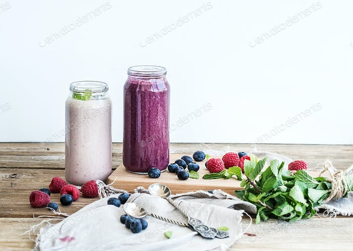Fresh healthy smoothie with blueberries, raspberries in glass jars and mint