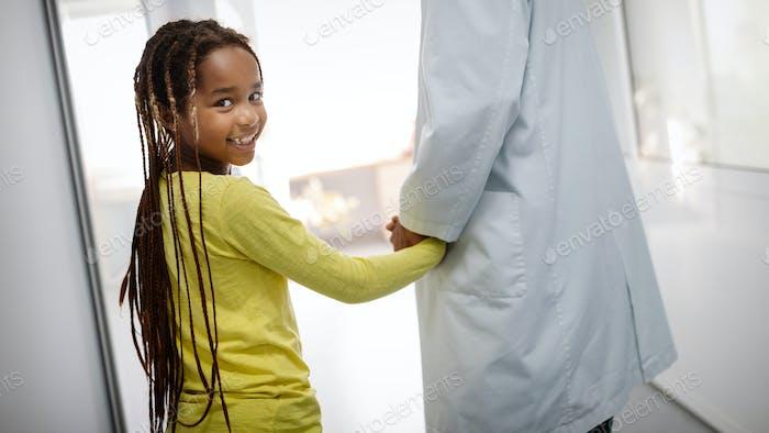 Kinderarzt Arzt lächelnd mit seinem kleinen Mädchen Patienten im Krankenhaus