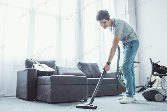 teenager vacuuming floor in living room with vacuum cleaner