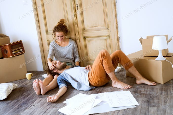 Young couple moving in new house, resting.