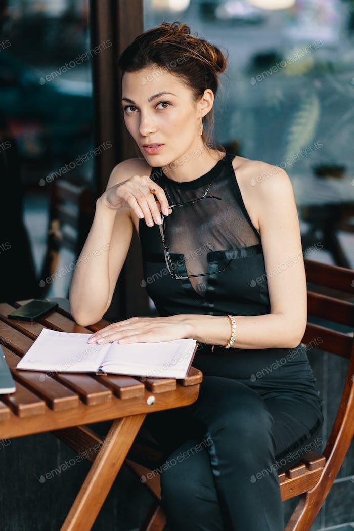 Raffinierte Geschäftsfrau in Brille, sitzt am Tisch im Café Arbeit am Laptop