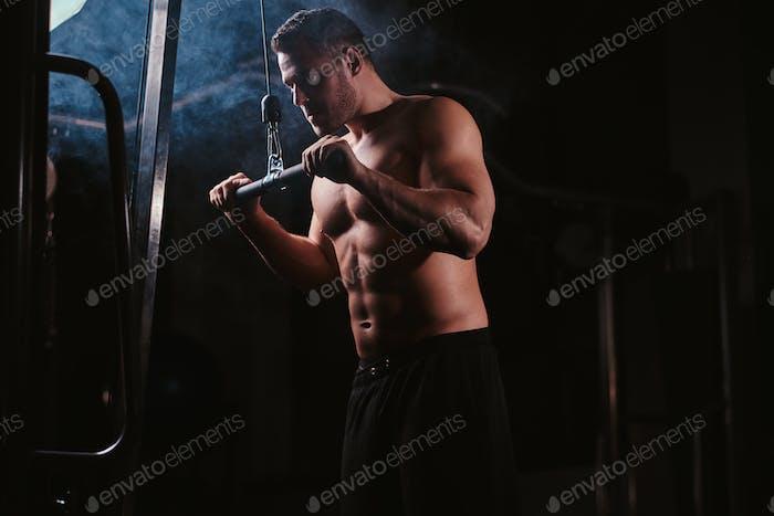 Fit-Sportler in einem dunklen Fitnessstudio umgeben von Rauch