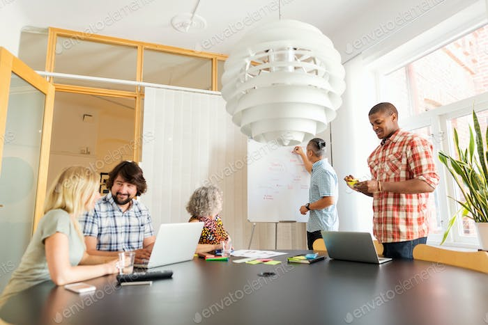 Coworkers discussing project in board room