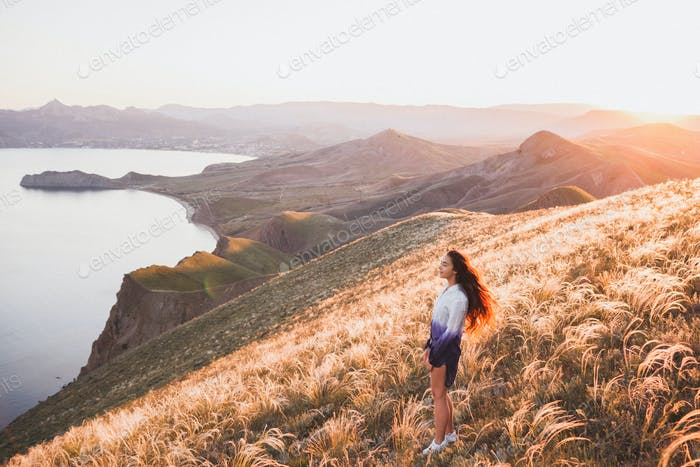 Young girl walking at nature and enjoying  view of the coast, field of feather grass