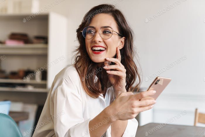 Smiling young beautiful woman using mobile phone