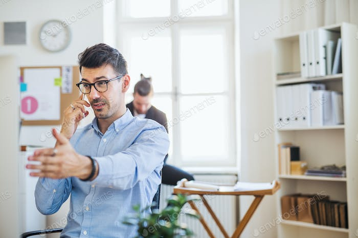 Young businessman with smartphone working in a modern office. Copy space.