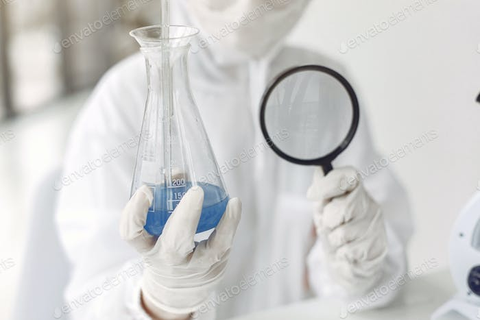 A laboratory scientist is examining blue solution in a bottle