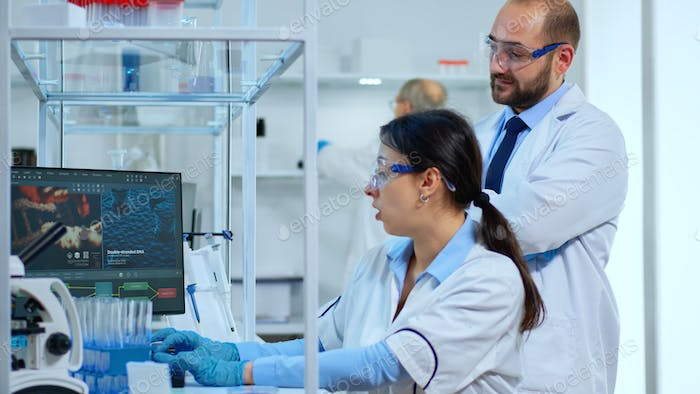 Research scientists working on computer with medical equipment