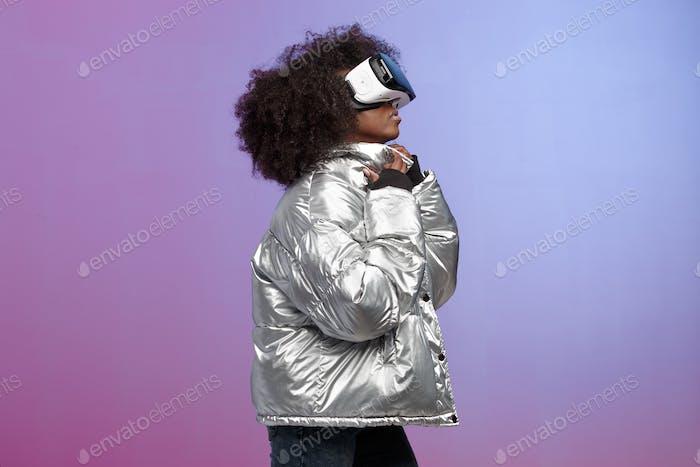 Trendy lockig braunhaarige Mädchen in einer silberfarbenen Jacke gekleidet verwendet die Virtual Reality Brille