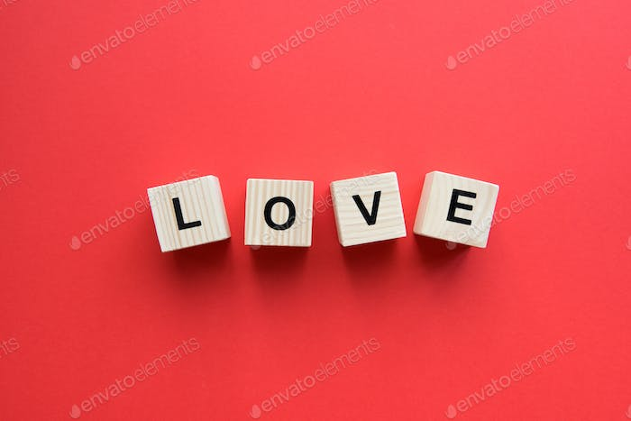 Top view of wooden cubes with love sign on red background