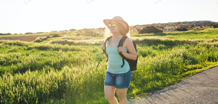 Traveler woman on nature. Concept of travel, hitch-hiking and vacation.