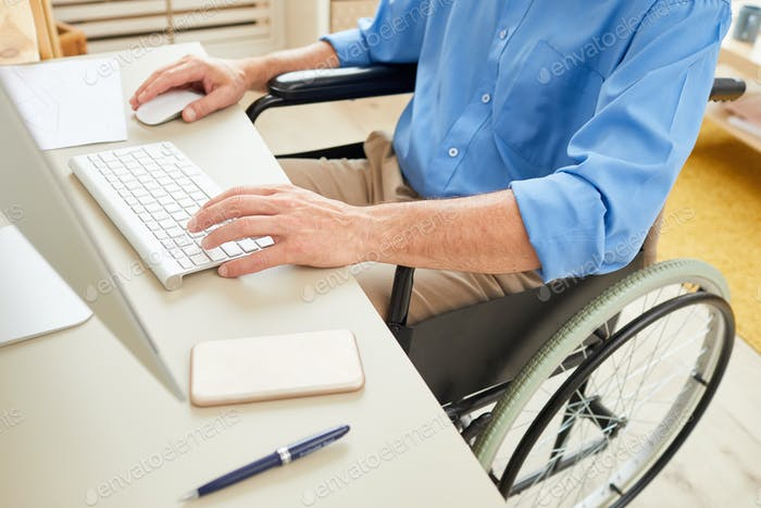 Disabled man typing on computer