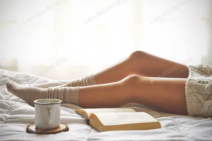 Soft photo of woman legs on the bed with old book and cup of cof