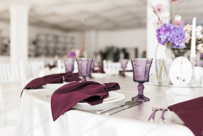 Close up photo of beautiful table setting at decorated wedding hall